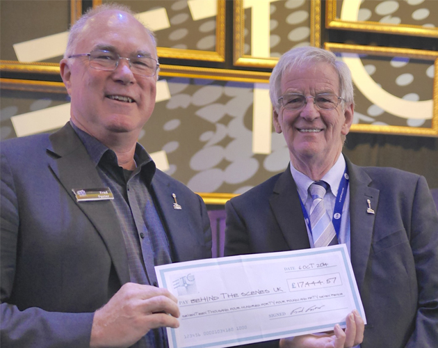 ETC CEO Fred Foster gives a check to Behind the Scenes Trustee John Simpson at the 2014 PLASA tradeshow